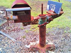 Old machinery parts make long lasting mailbox stands - photo by Vivienne Tracy