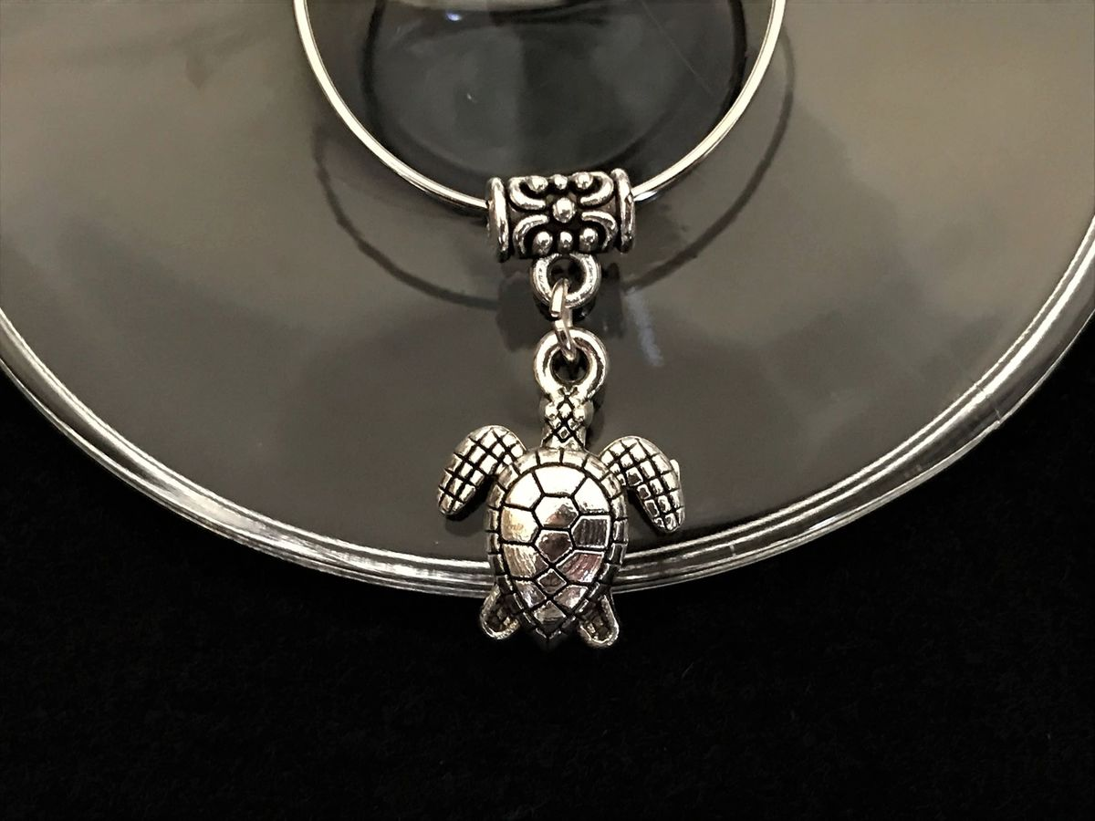 Never lose your glass at a party with this silver turtle wine glass charm. - Available at